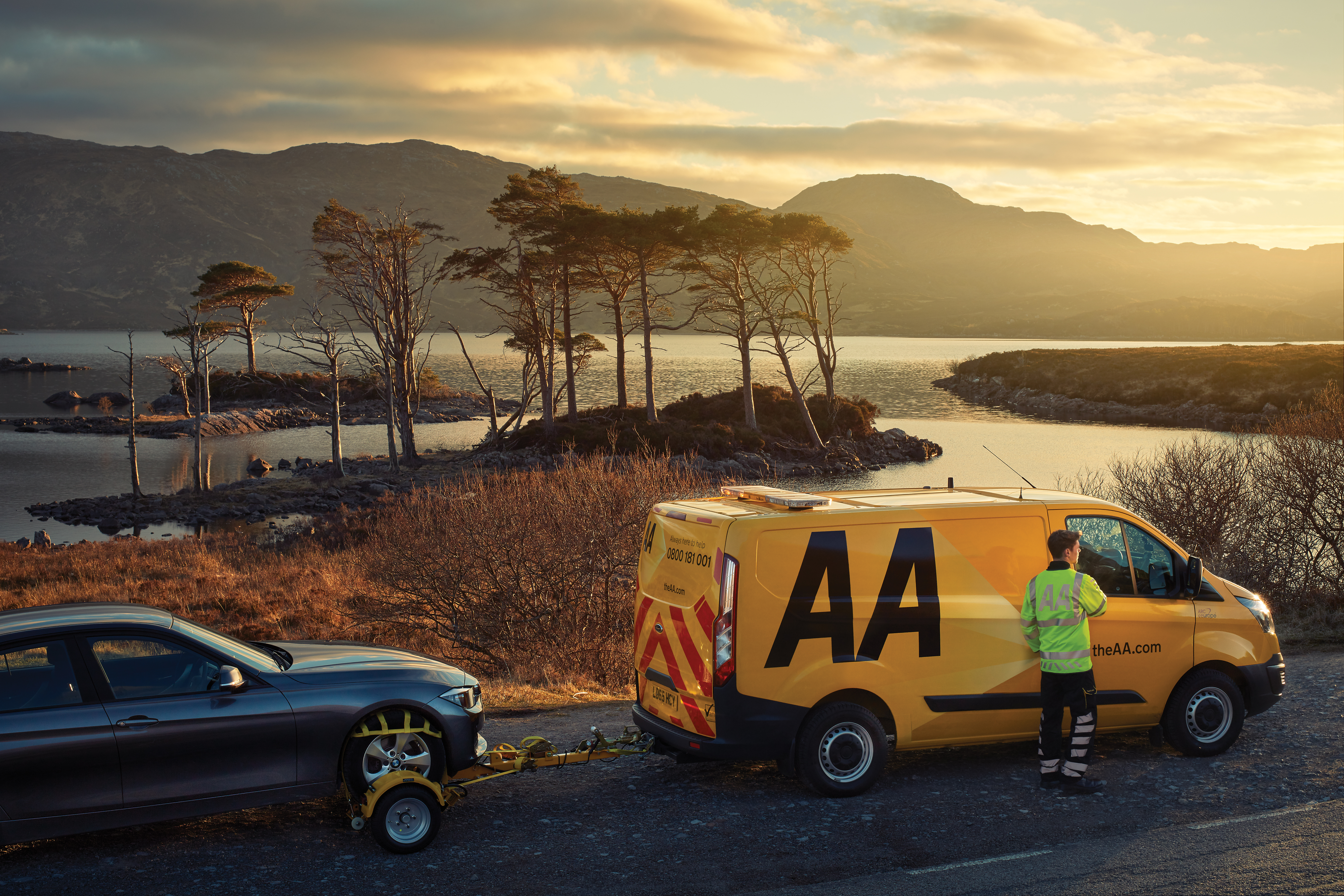 AA recovery van towing a car at side of rural road
